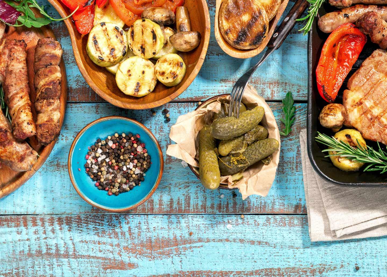 Tisch mit Grillfleisch und Grillgewürzen